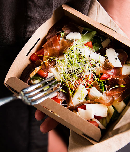 A salad in a takeout container.